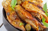 picture of thighs  - Crispy Roasted Chicken Thighs with Tomatoes Green Olives and Basil closeup in Black Fry Pan  - JPG
