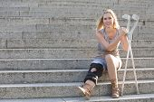 picture of crutch  - blonde woman with crutches sitting on stairs - JPG