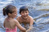 stock photo of little sister  - Little boy teaches his little sister to swim in a lake - JPG