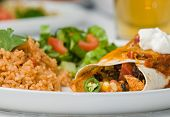 stock photo of enchiladas  - Gourmet Mexican taco burrito or enchilada with black beans chicken lettuce tomatoes cheddar cheese salsa sour cream and jalapeno peppers accompanied by salad Spanish rice and beer