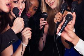 pic of karaoke  - Portrait of happy multiethnic friends singing into microphones at karaoke party - JPG