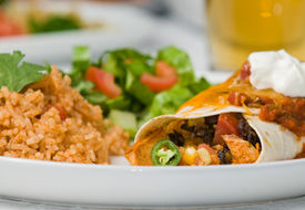 image of enchiladas  - Gourmet Mexican taco burrito or enchilada with black beans chicken lettuce tomatoes cheddar cheese salsa sour cream and jalapeno peppers accompanied by salad Spanish rice and beer
