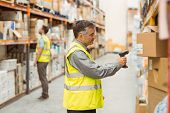 foto of barcode  - Warehouse worker scanning barcode on box in a large warehouse - JPG