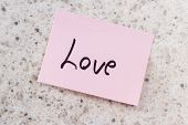 image of office romance  - small pink note with the word love on an office desk background - JPG
