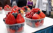 image of anonymous  - Fresh fruit berries with anonymous people in the background - JPG