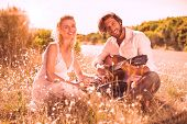 picture of serenade  - Handsome man serenading his girlfriend with guitar on a sunny day - JPG