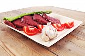pic of flank steak  - fresh raw beef meat steak fillet on wooden plate with asparagus and tomatoes ready to prepare - JPG