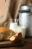 picture of milk products  - Retro can for milk with fresh bread and glass of milk on wooden background - JPG