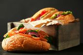foto of sandwich  - Sandwiches with salmon in wooden box on dark wooden background - JPG