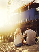 picture of couple sitting beach  - romantic couple sitting on beach with creative lens flare - JPG