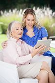 picture of granddaughter  - Smiling grandmother and granddaughter using tablet computer at nursing home porch - JPG