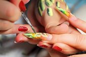 image of nail-design  - Master draws design floral on female nails.