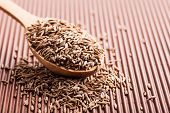 picture of cumin  - spice cumin in a wooden spoon on a brown background - JPG
