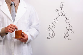 pic of ozone layer  - Man in a white lab coat holding a cup and a plate next to a drawing of the ozone formation - JPG