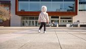 foto of hoodie  - Back view of little girl with sneakers and hoodie standing in a city square on a sunny day - JPG