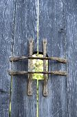 picture of peep hole  - Old wooden door with metal grid peephole in sunny day - JPG