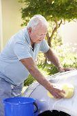stock photo of car carrier  - Senior Man Washing Car In Drive - JPG