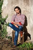 picture of wooden crate  - Smiling male model sitting on wooden crate with legs crossed - JPG