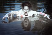 picture of bloody  - Beautiful vampire woman dressed white bloody shirt standing in the river - JPG