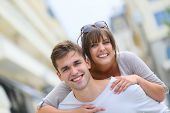 foto of piggyback ride  - Young man giving piggyback ride to girlfriend in town - JPG