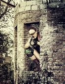 picture of sniper  - Young woman sniper sitting in ruins with automatic - JPG