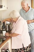stock photo of hot couple  - Retired Senior Couple In Kitchen Making Hot Drink Together - JPG