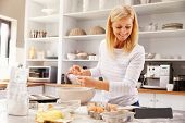 picture of follow-up  - Woman baking at home following recipe on a tablet - JPG