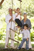 stock photo of tree house  - Grandchildren And Grandparents Standing By Tree House In Garden - JPG