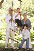 foto of grandparent child  - Grandchildren And Grandparents Standing By Tree House In Garden - JPG