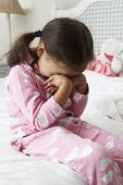 stock photo of pajamas  - Tired Young Girl Wearing Pajamas Sitting On Bed - JPG