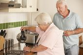 picture of hot couple  - Retired Senior Couple In Kitchen Making Hot Drink Together - JPG