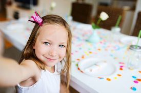 image of princess crown  - Adorable little girl with princess crown at kids birthday party making selfie - JPG