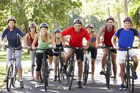 image of fifties  - Group Of Cyclists On Cycle Ride Through Park - JPG