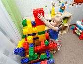 Persistent Little Girl Building Big Block Tower In Daycare poster