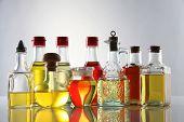 palm oil, sesame seed oil, olive oil, grape seed oil and corn oil in  glass bottle over white backgr poster