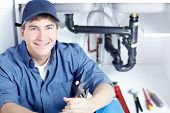 stock photo of janitor  - Mature plumber fixing a sink at kitchen - JPG