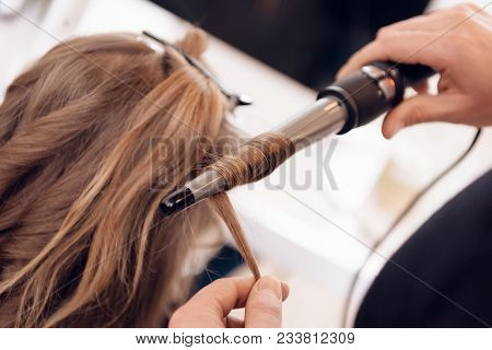poster of Close Up. Brown Hair Woman Does Curling Hair In Beauty Salon. Hairdresser Make Hair Wave For Woman.