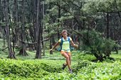 Trail runner woman athlete running jumping in forest nature mountains background. Sport girl active  poster