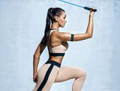 Strong Woman Using Resistance Band In Her Exercise Routine. Photo Of Fitness Model Workout On Grey B poster