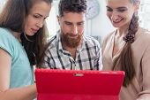Reliable digital nomads cooperating for helping their co-worker during remote work on a tablet PC in poster