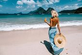 Back view of woman relaxing on the tropical beach, looking at sea landscape and drinking juice. Trav poster