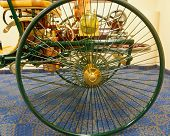 picture of motor coach  - Wheel of antique horseless carriage on blue carpet - JPG