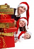 stock photo of christmas-present  - Isolated studio shot of happy young family of three wearing Santa - JPG