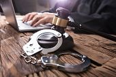 Close-up Of Handcuffs And Gavel In Front Of Judge Working On Laptop poster