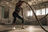 Fitness Woman Using Training Ropes For Exercise At Gym. Athlete Working Out With Battle Ropes At Cro poster