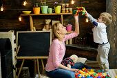Nursery With Chalkboard On Background. Mother And Son Play With Constructor. Motherhood Concept. Fam poster