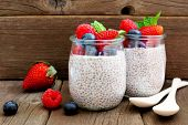 Healthy Berry Chia Pudding In Jars. Scene On A Rustic Wood Background. poster