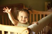 stock photo of waving hands  - Baby girl waving hand and standing up in crib - JPG