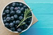 Fresh Ripe Wild Blueberries In White Bowl On Blue Wood Table. Fresh Blueberry In Top View Flat Lay W poster