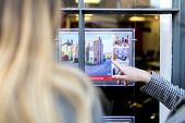 Couple Looking And Pointing At A Property Advert In The Window Of An Estate Agents Or Real Estate Sh poster